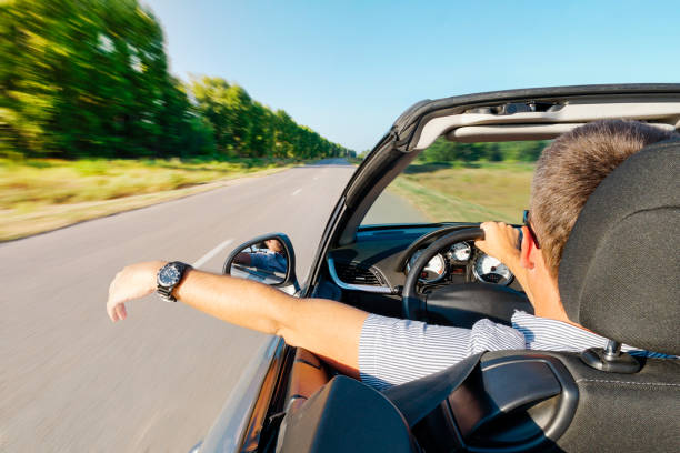 calm happy successful man sit in car hand is driving the car on the road. young guy inside an expensive convertible is driving on a road outside city against backdrop of beautiful summer nature. stock photo