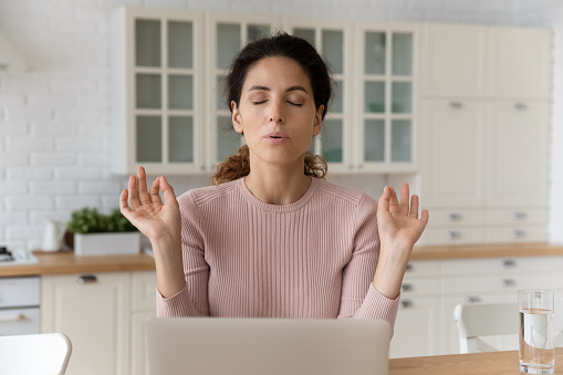 Home office yoga. Calm millennial hispanic female freelancer sit by pc with closed eyes breath deep meditate. Mindful young woman relax from online work doing breathing exercises join fingers in mudra