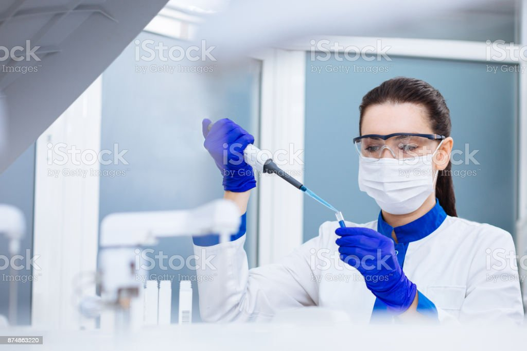 Calm laboratory assistant analyzing sample stock photo
