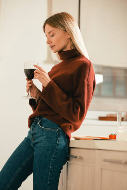 Calm lady thoughtfully looking at the glass of wine stock photo