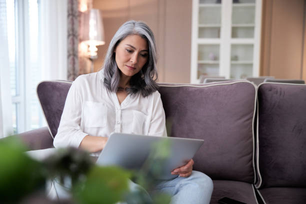 Calm lady with gadget working at home stock photo stock photo