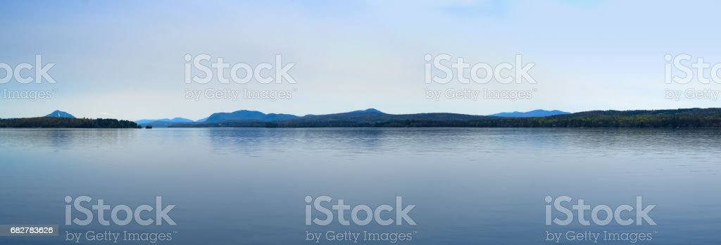 calm lake blue sky and water mountains Magog Québec stock photo