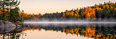 Swedish lake in autumn colors. Early morning lake with a little fog or mist still left.