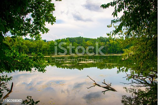 A calm lake with a reflection of the clouds in the water and framed by trees