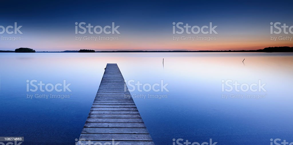 Calm Lake with Boardwalk Dock at Sunset royalty-free stock photo