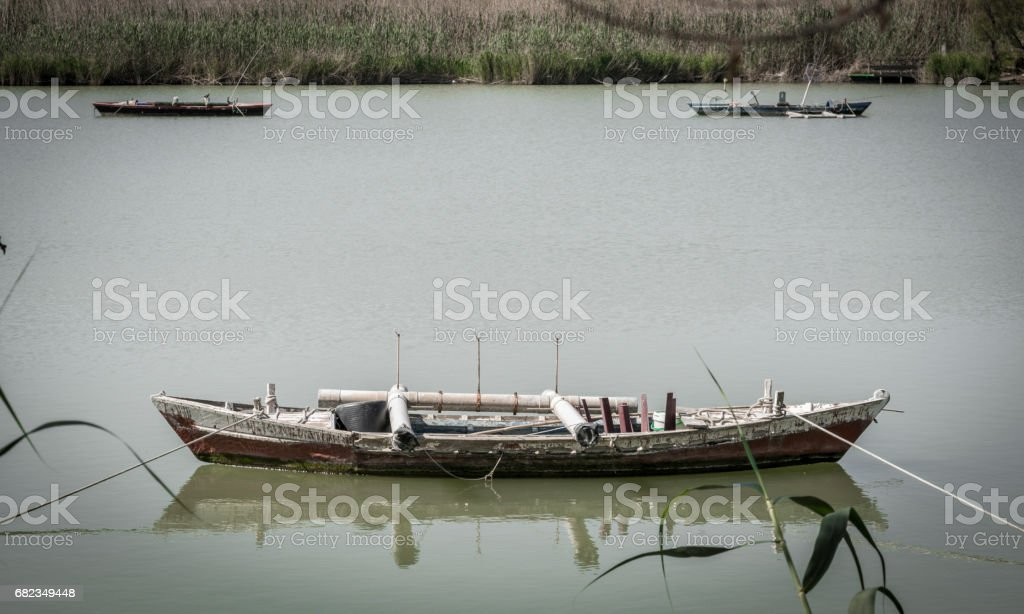 Calm lake with fishing boats. Fresh water lagoon in Estany de cullera. Valencia, Spain royalty free stockfoto