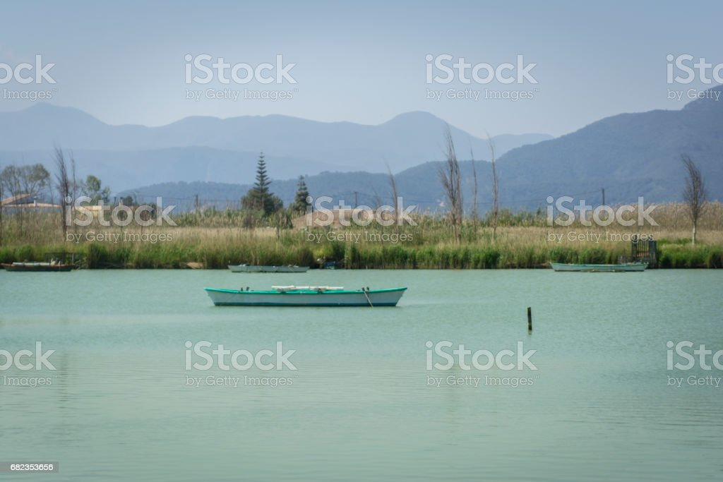 Calm lake with fishing boats. Fresh water lagoon in Estany de cullera. Valencia, Spain royalty free stockfoto