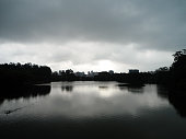 Calm lake with reflections of a bright but cloudy sky. Forest surrounding the lake and some buildings in the background.
