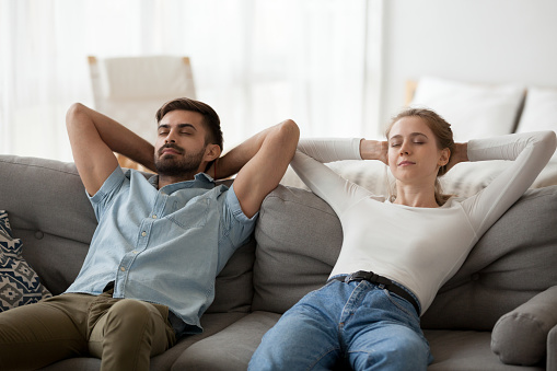 973962076 istock photo Calm lazy couple relaxing on comfortable sofa resting together 1124667798