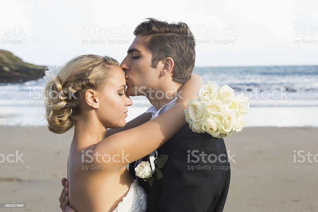 Calm lovely young bridegroom kissing his wife on the brow stock photo