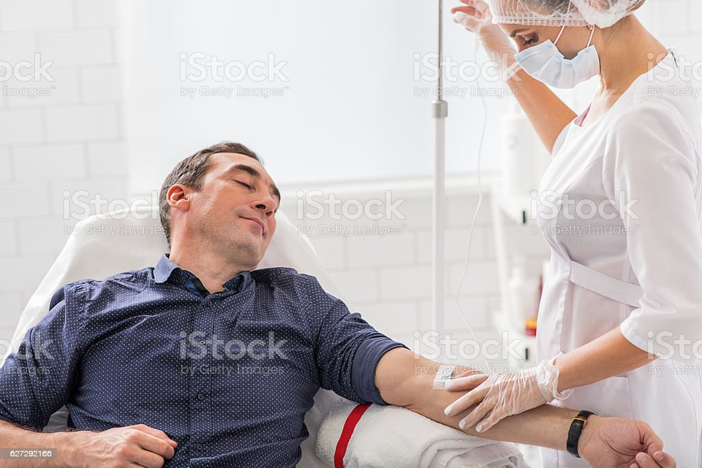 Calm male patient getting drip treatment stock photo
