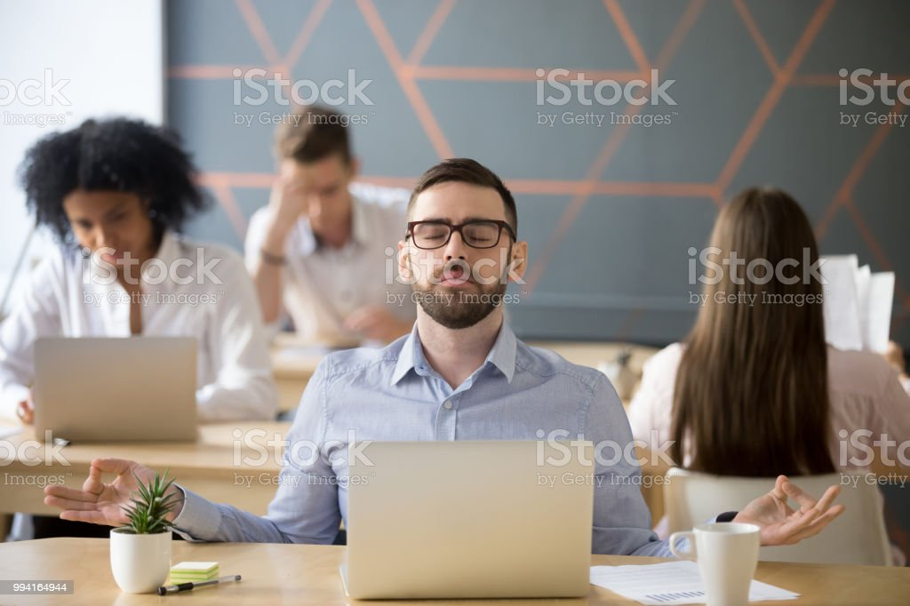 Calm male worker meditating in lotus position at workplace stock photo