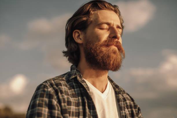 ruhiger mann meditiert am sonnigen sommertag - augen geschlossen stock-fotos und bilder