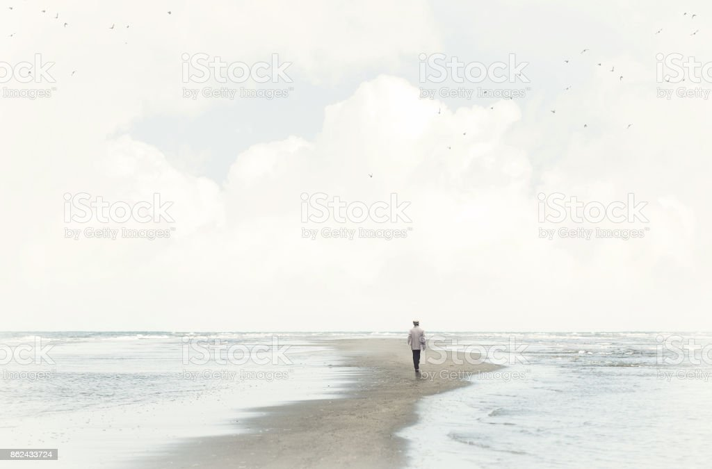 calm man walking in the sand between two seas stock photo