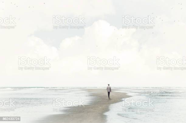 Photo of calm man walking in the sand between two seas