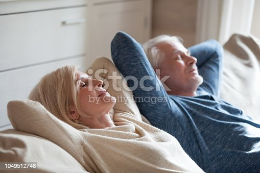 istock Calm mature couple relaxing on sofa having daytime nap together 1049512746