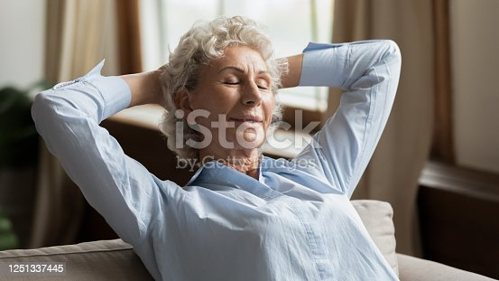 973962328 istock photo Calm mature woman puts hands behind head resting at home 1251337445