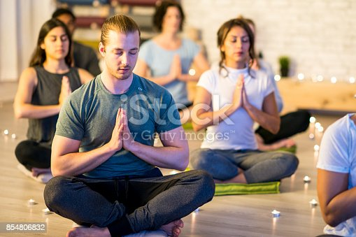 A multi-ethnic group of adults are indoors in a fitness studio. They are wearing casual exercise clothing. They are sitting on cushions in a candlelit room and they are meditating with their eyes closed. A Caucasian man is in focus.