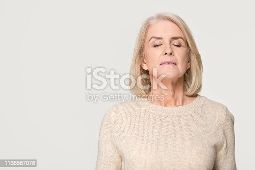 istock Calm mid aged woman breathing fresh air isolated on background 1135587078