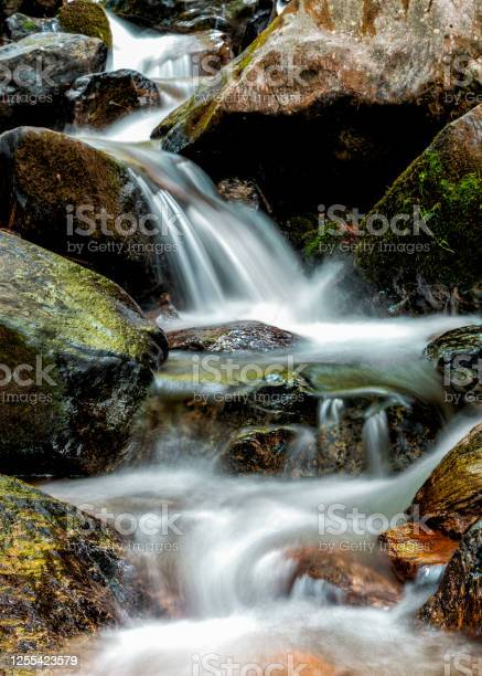 Photo of calm mountain stream rapids over colrful rocks and stones