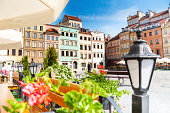 Warsaw old town marketplace square, street lamp in cafe and flowers on foreground