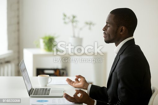 916520034istockphoto Calm peaceful african-american businessman in suit meditating at office work 916520058