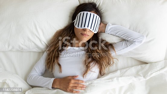 Calm peaceful mixed race young lady wearing sleeping mask, enjoying night dream, napping in comfortable bed at home. Top above view serene biracial millennial woman relaxing on pillow under blanket.