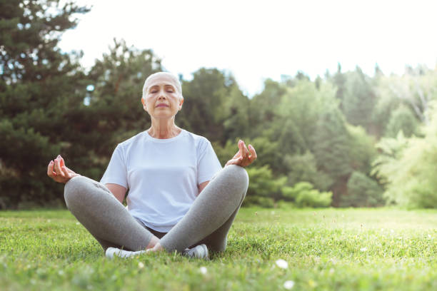 Calm peaceful woman meditating Peace and relaxation. Calm nice peaceful woman sitting on the grass and closing her eyes while meditating lotus position stock pictures, royalty-free photos & images