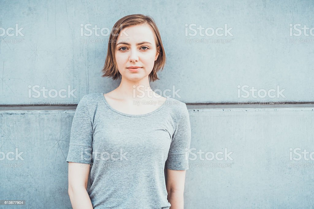Calm pretty woman leaning against concrete wall stock photo