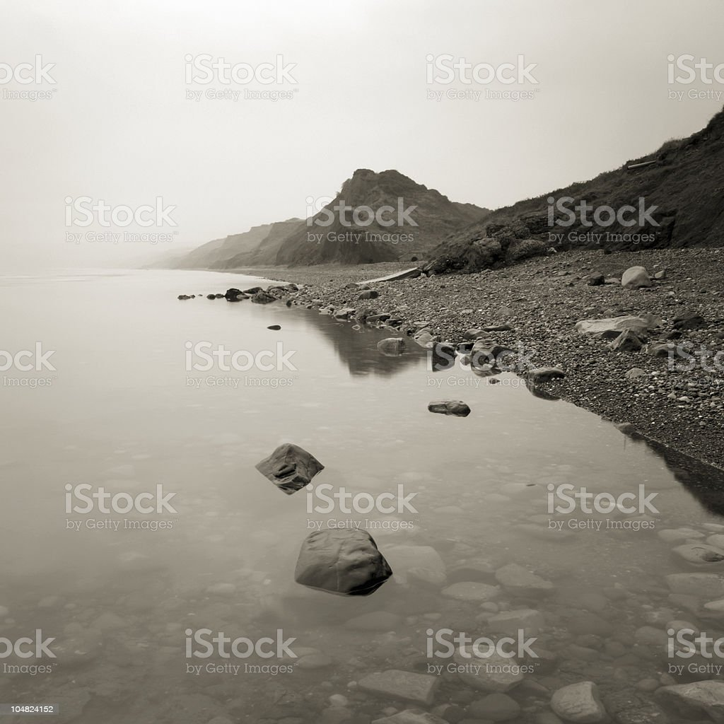 Calm sea by coast in mist royalty-free stock photo