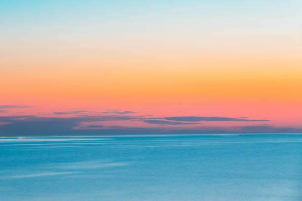 lugna havet eller ocean och färgsprakande solnedgång eller soluppgång himmel bakgrund. varma och kalla färger - pink sunrise bildbanksfoton och bilder