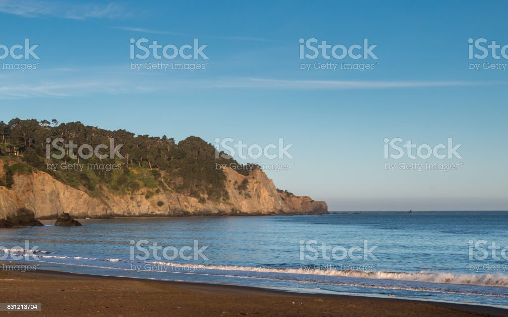 Calm Sea Waters with Vegetation on Cliff in the Background stock photo