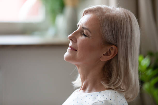 Calm serene middle aged woman breathing with eyes closed Calm serene middle aged woman meditating with eyes closed inhaling fresh air relaxing indoors, happy healthy old mature lady enjoying resting feel peace of mind doing breathing yoga exercises at home deep stock pictures, royalty-free photos & images