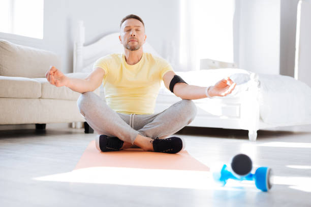 Calm serious man practicing meditation Biohacking meditation. Nice pleasant charming man sitting on floor while closing eyes and trying medication biohacking stock pictures, royalty-free photos & images