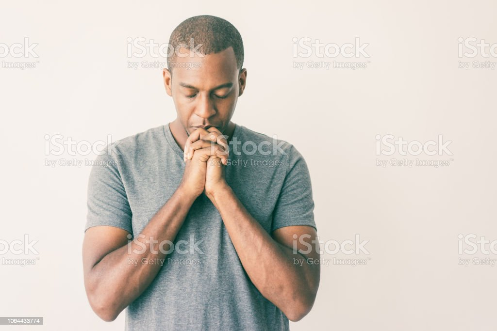 Calm spiritual handsome African guy praying with closed eyes stock photo