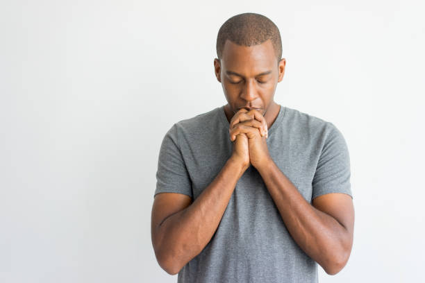 Calm spiritual handsome African guy praying with closed eyes Calm spiritual handsome African guy praying with closed eyes. Serious peaceful young man with joining hands meditating. Belief concept relief emotion stock pictures, royalty-free photos & images