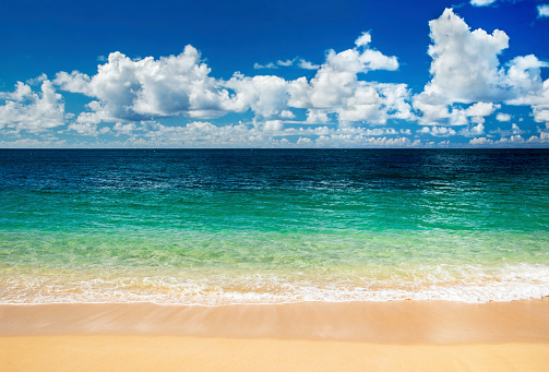 Peaceful summer day at Sunset Beach on the North Shore of Oahu, Hawaii, looking toward Banzai Pipeline, better known for its huge, reef-break waves in winter.