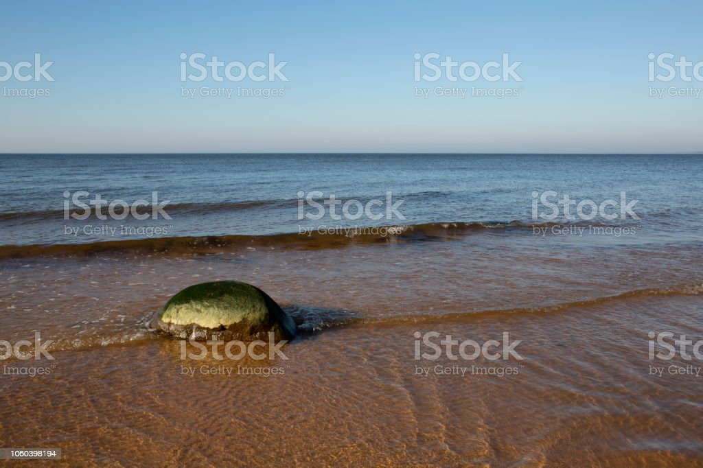 Calm sunny autumn Baltic Sea landscape with lonely stone stock photo