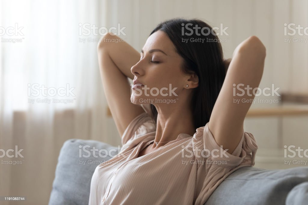 Calm tired young woman attractive face lounge leaning on sofa napping...