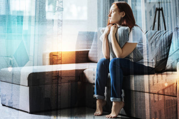 Calm upset woman hugging a pillow and looking aside stock photo
