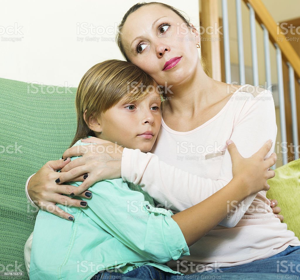 Calm woman consoling sad teenage son at home