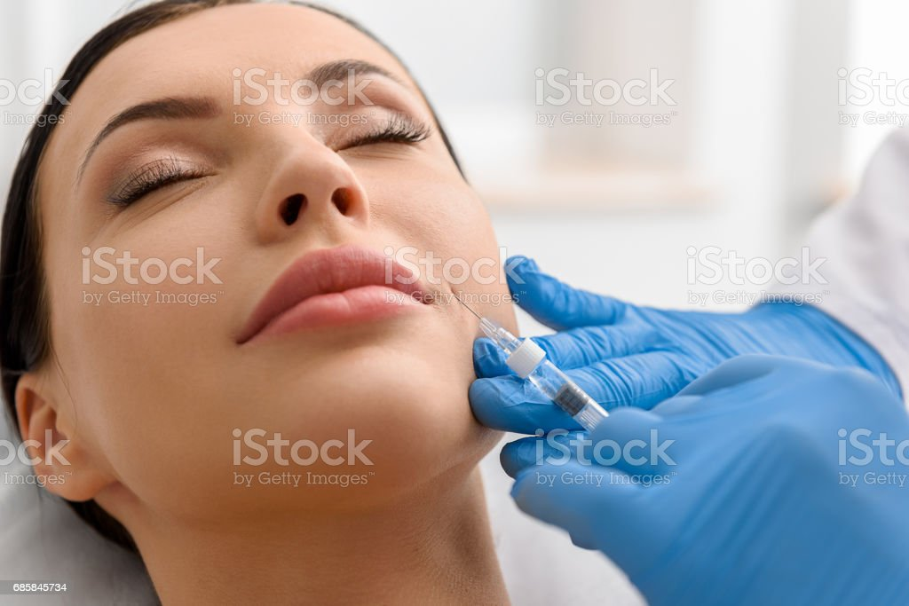 Calm woman during injection in face - foto de stock