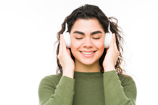 Peaceful latin young woman with wireless headphones relaxing and chilling while listening to music