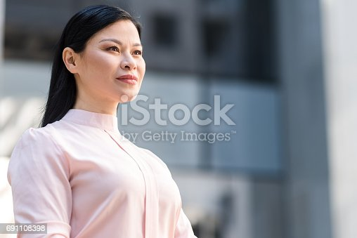 Low angle portrait female expressing tranquility while standing in street. She looking away