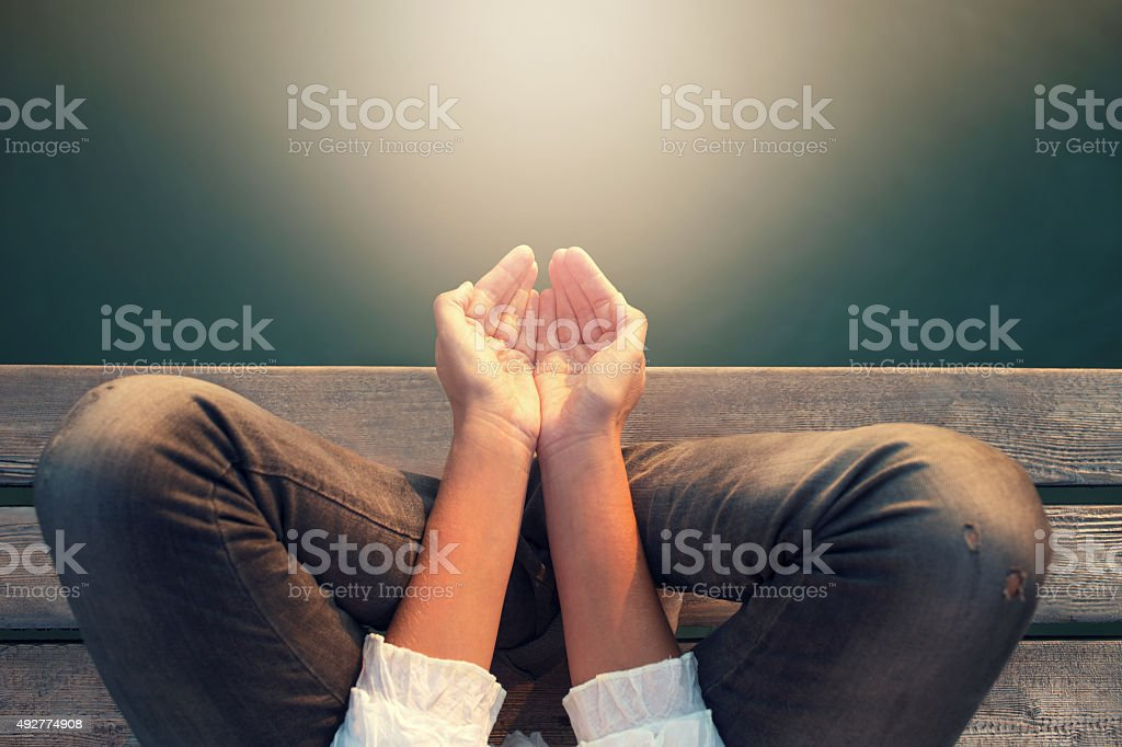 calm woman meditating reciving power by light stock photo