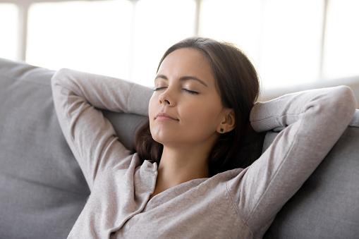 Mujer tranquila poniendo las manos detrás de la cabeza apoyada en un cómodo sofá ...