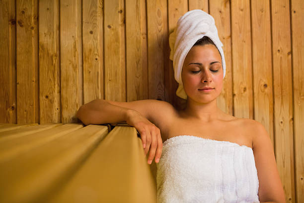 Calm woman relaxing in a sauna Calm woman relaxing in a sauna wearing white towels sauna stock pictures, royalty-free photos & images