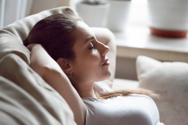 calm woman relaxing on sofa hands over head - resting stock pictures, royalty-free photos & images