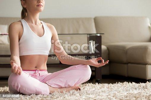 istock Calm young woman practicing yoga, enjoying meditating alone at home 845516398