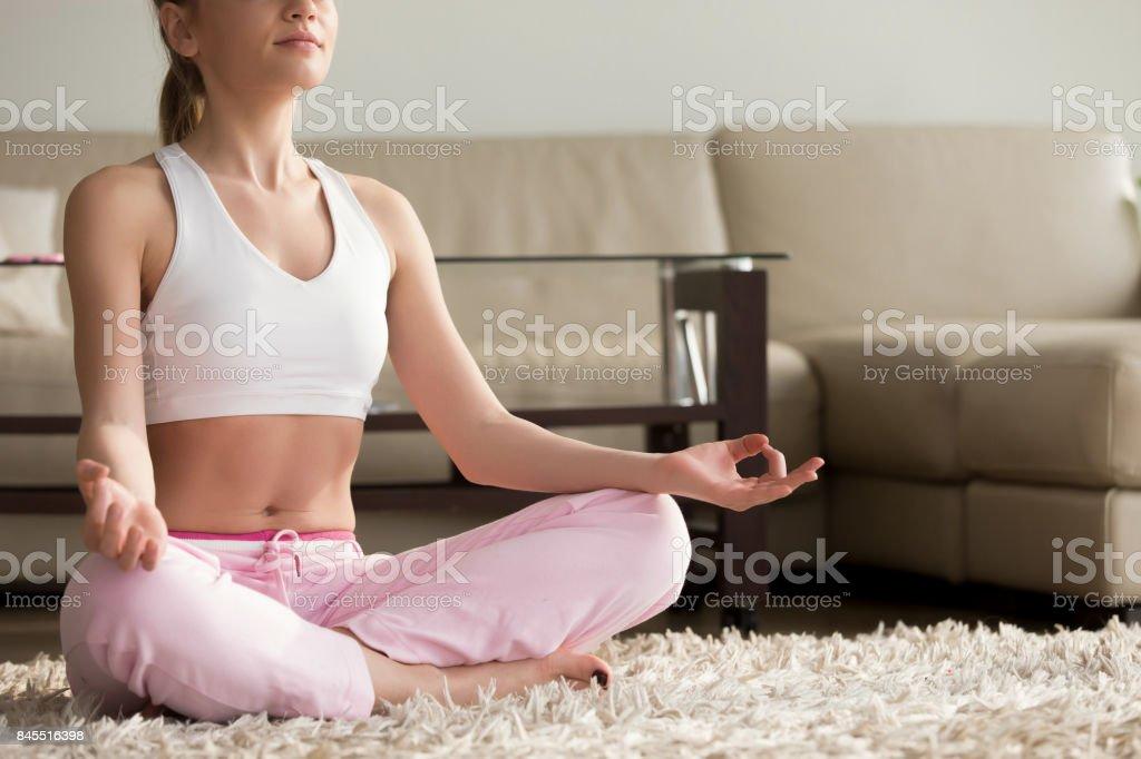 Calm young woman practicing yoga, enjoying meditating alone at home stock photo